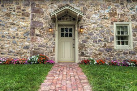 11959782-Percorso-e-porta-d-ingresso-di-una-casa-in-pietra-con-fiori-e-prato-lussureggiante--Archivio-Fotografico
